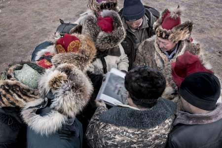 BTS, Kazakh men looking at Jimmy's book Kazakh, Sagsai,Bayan-Ӧlgii province, Mongolia, 2017